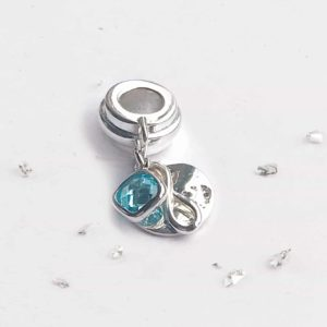 Charm with Infinity Knot and Light Blue Birthstone
