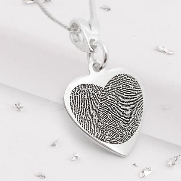 Silver heart necklace with heart shaped fingerprint engraving close up