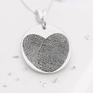 Silver round necklace with heart shaped fingerprint engraving close up