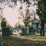 Man standing over a grave at a funeral
